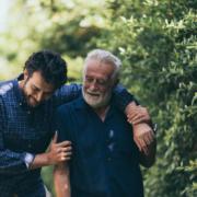 Vater und Sohn laufen zusammen neben einer grünen Hecke